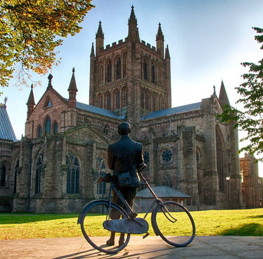 A bronze statue of Edward Elgar admiring Hereford Cathedral
